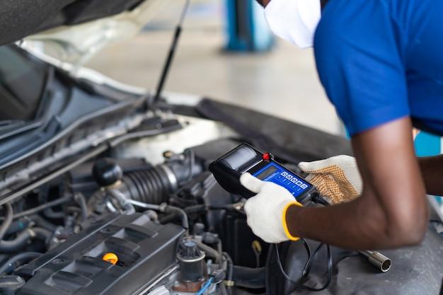 自動車修理ガレージで働く専門の整備士。バッテリー検査。バッテリー容量テスター電圧計をチェックしている黒人男性の整備士の車。