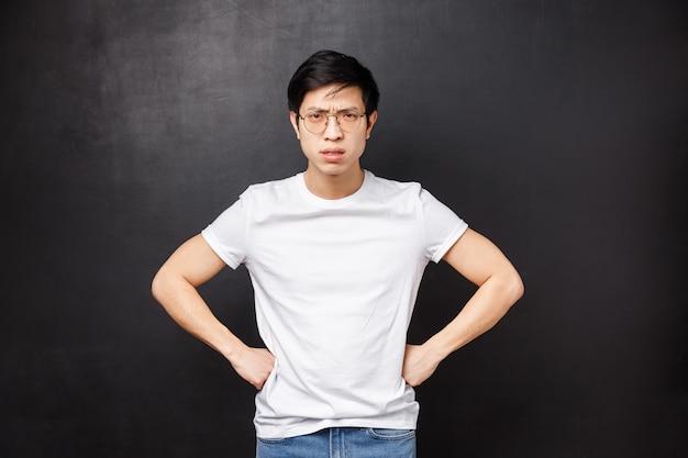Объясни себя сейчас. серьезно выглядящий сердитый и недовольный азиатский старший брат ругает брата и сестру за то, что они играют поздно, держат руки за талию и разочарованно нахмурились, земляной ребенок наказывает