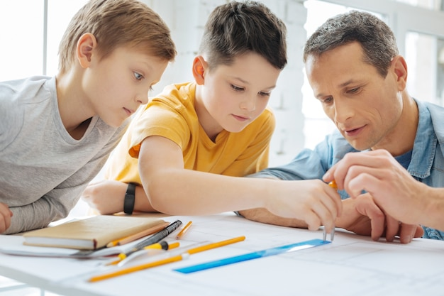 Explaining clearly. caring young father holding a compass and showing his sons how to use it correctly, measuring the distance on the blueprint