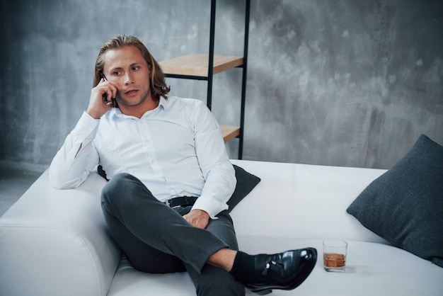 Explaining the details. portrait of young businessman with long hair sitting on couch and talking on mobile phone with whiskey on right side