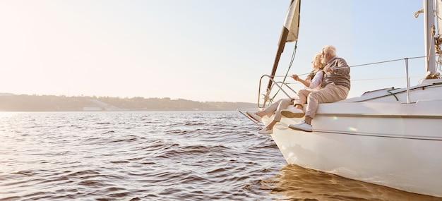 穏やかな青い海の男に乗って帆船の横に座っている幸せな年配のカップルの夢を探る