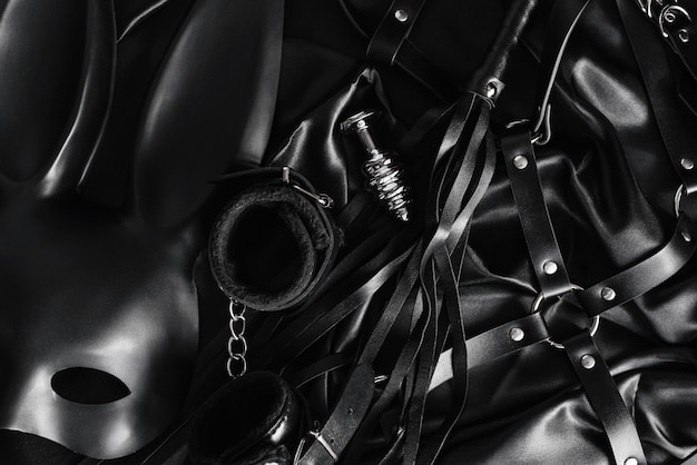 Explore the world of kinky play. top view of bdsm leather kit against of a black silk.