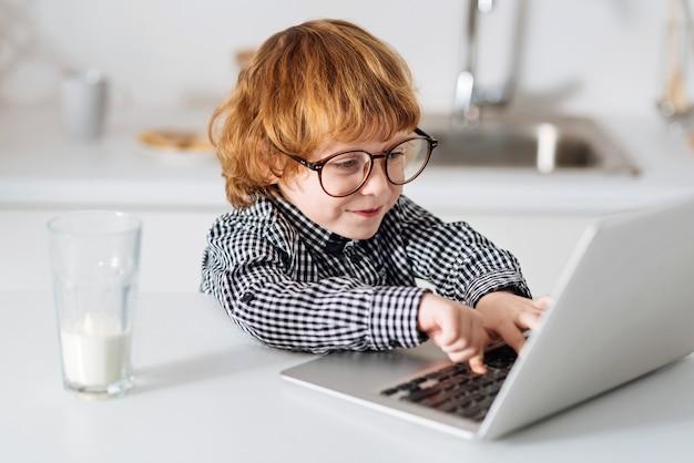 アイデアを探る。眼鏡をかけ、太陽に照らされたキッチンのテーブルに座ってラップトップでテストを入力する面白い賢い赤毛の少年
