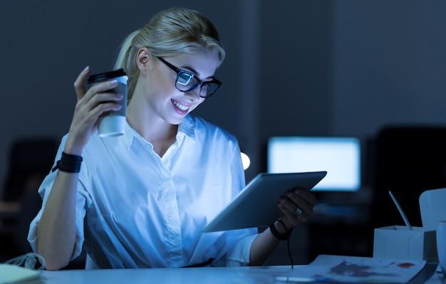 새로운 아이디어 탐색. 프로젝트에서 작업하는 동안 사무실에 앉아서 태블릿을 사용하는 긍정적 인 젊은 미소 it 여자