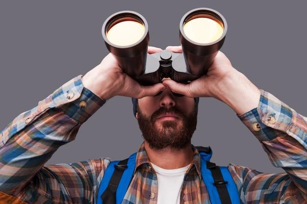 새로운 장소를 탐색합니다. 회색 배경에 서 있는 동안 배낭을 메고 쌍안경을 통해 바라보는 자신감 있는 수염 난 남자