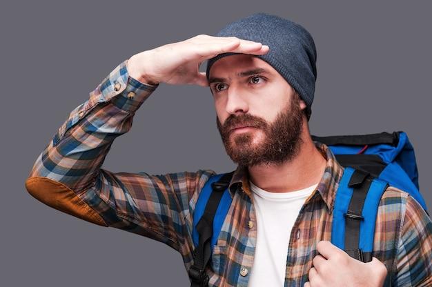 새로운 장소를 탐색합니다. 수염을 기른 잘생긴 남자가 배낭을 메고 눈에 손을 대고 회색 배경에 서서 전망을 바라보고 있다