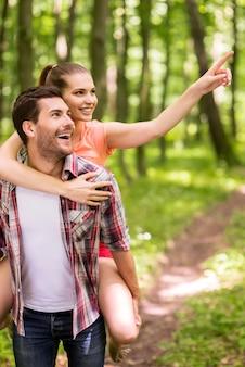 공원 쪽을 탐색합니다. 여자가 남자를 껴안고 미소로 가리키는 동안 공원에서 산책하는 행복한 젊은 사랑의 커플