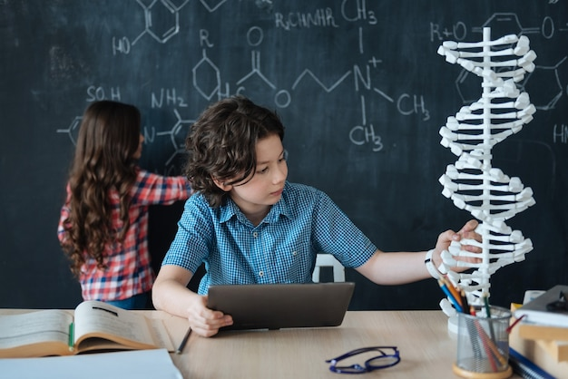 Вместе изучаем науку. любопытно - способные подростки сидят в школе и наслаждаются уроком химии, пишут на доске и используют планшет.