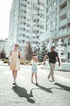 도심 탐험. 두 부모와 딸이 손을 잡고 내리막길을 걷고 있는 행복한 가족입니다.