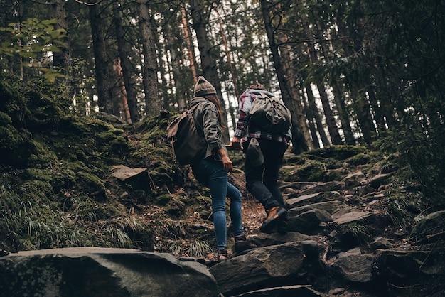 Изучение природы. молодая пара, поднимающаяся вверх во время прогулки в лесу, вид сзади в полный рост