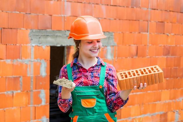 도구 탐색 미래 엔지니어 행복한 아이는 건물 수리를 위해 벽돌을 사용합니다.