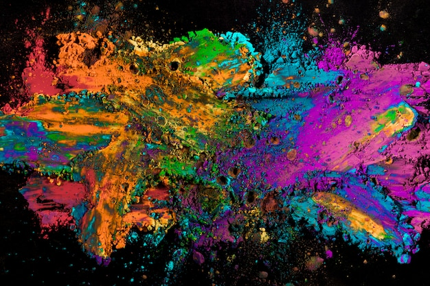 Explosion of colored powder on black surface