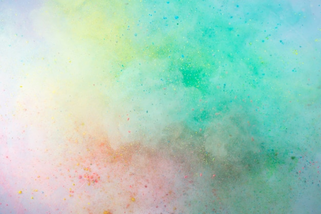 Explosion of colored powder on white background