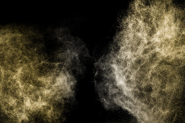 Explosion of gold powder on black background