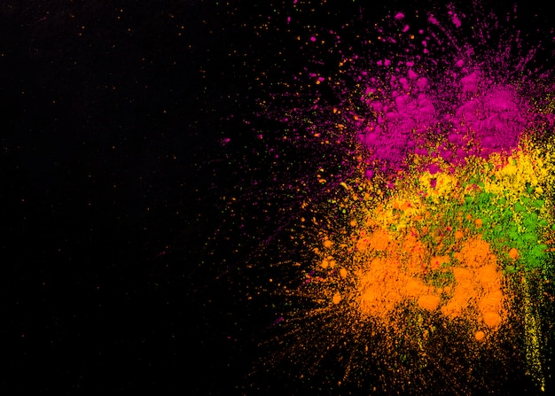 Explosion of holi colors on dark background