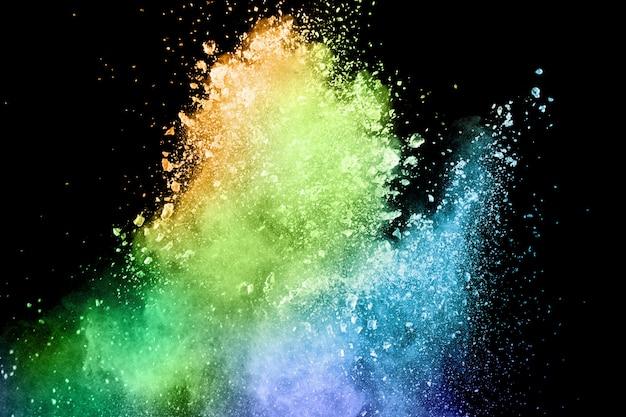 Взрыв цветной порошок на черном фоне. всплеск цветной порошок пыли на темном фоне.