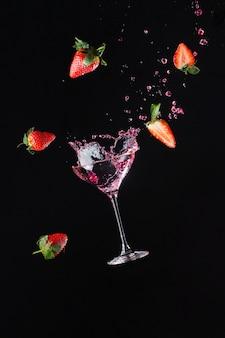 Взрыв свежести с бокалом прохладного вина. черный фон
