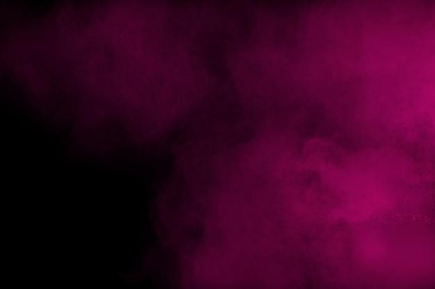 Взрыв розового цвета порошка, изолированные на черном фоне.