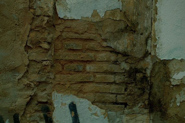 Exposed brickwork texture on an old damaged wall with cracked missing plaster
