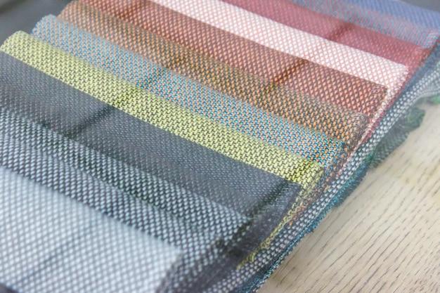 Экспозиция образцов тканей разных цветов через витрину магазина.