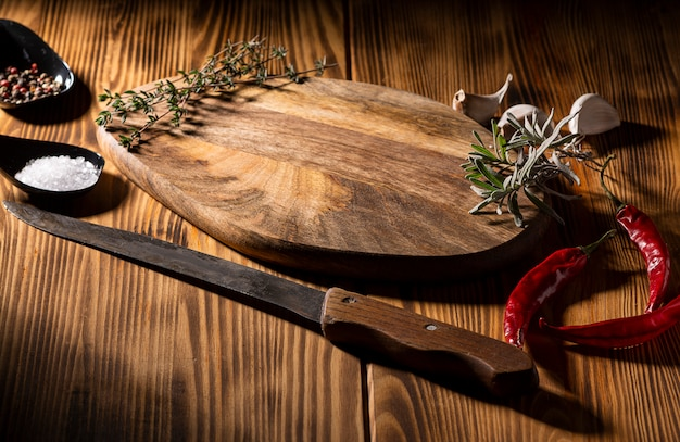 Exposition of wooden table with knife, chili pepper, garlic and pepper on wooden table