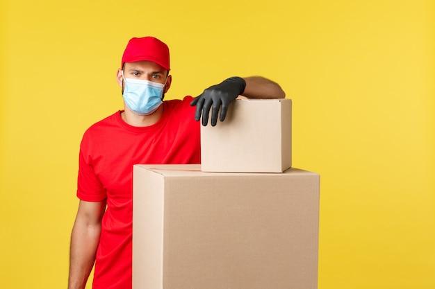 Экспресс-доставка во время пандемии, covid-19, безопасная доставка, концепция покупок в интернете. красивый курьер в красной форме и медицинской защитной маске, опирается на кучу ящиков, отправляя заказы