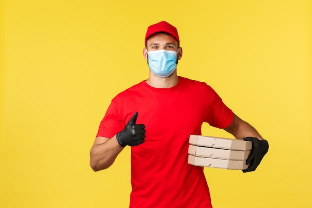 Экспресс-доставка во время пандемии, covid-19, безопасная доставка, концепция покупок. дружелюбный молодой курьер в красной форме и медицинской маске, обеспечивает безопасную доставку заказа, держит пиццу и показывает большой палец вверх