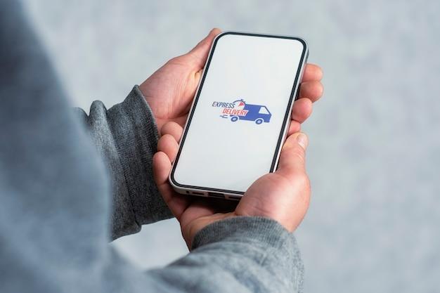 휴대 전화로 빠른 배송. 남자는 그의 손에 흰색 화면에 아이콘이있는 스마트 폰을 보유하고 있습니다.