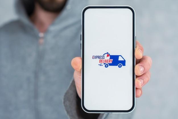 휴대전화로 신속하게 배송하세요. 한 남자가 손에 흰색 화면에 아이콘이 있는 스마트폰을 들고 있습니다.