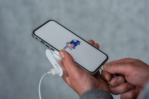 휴대전화로 신속하게 배송하세요. 한 남자가 손에 흰색 화면에 보조 배터리와 아이콘이 있는 스마트폰을 들고 있습니다.