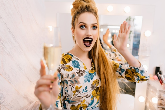 美容室で贅沢な髪形、美しいメイク、シャンパングラスでスタイリッシュな可愛いモデルの明るい感情を表現