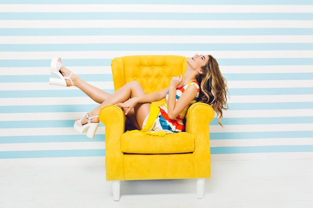 Expressing brightful positive emotions of joyful fashionable young woman in colorful dress having fun in yellow chair isolated on striped blue white wall. summer time, joy, smiling, happiness.