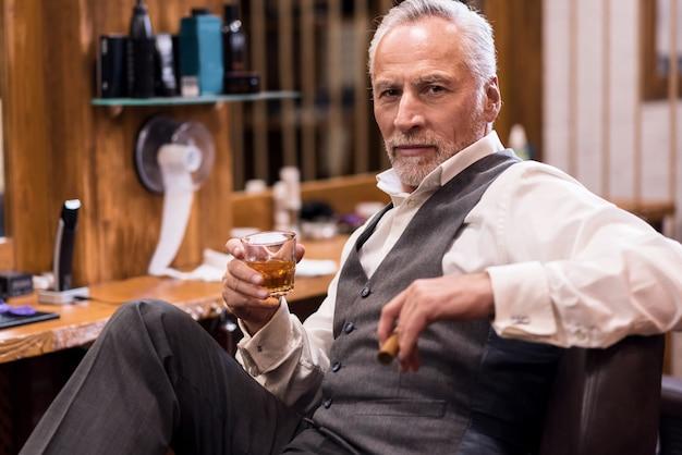 自信を表現し、コニャックガラスと葉巻と革張りのアームチェアに座って豪華なスーツを着ている魅力的な年配の男性。