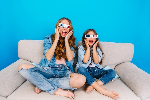 Expressing crazy happy true emotions to camera of fashionable mother and her daughter in jeans clothes on couch isolated on blue background. wearing 3d glasses, having fun together
