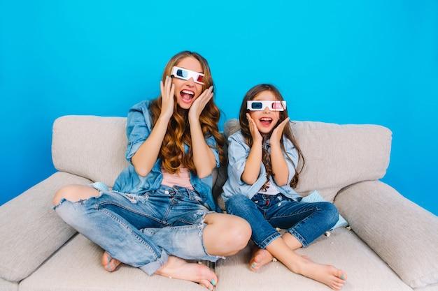 青の背景に分離されたソファの上のおしゃれな母とジーンズの服で彼女の娘のカメラに狂気の幸せな真の感情を表現します。 3dメガネをかけて一緒に楽しむ