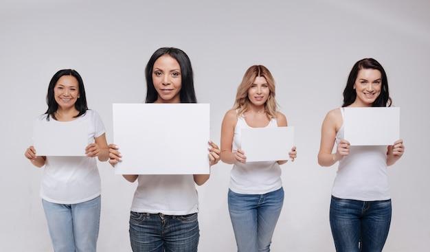 Выражаем наши желания. харизматичная мотивация симпатичных дам в одинаковой одежде и с одинаковыми знаками во время позирования