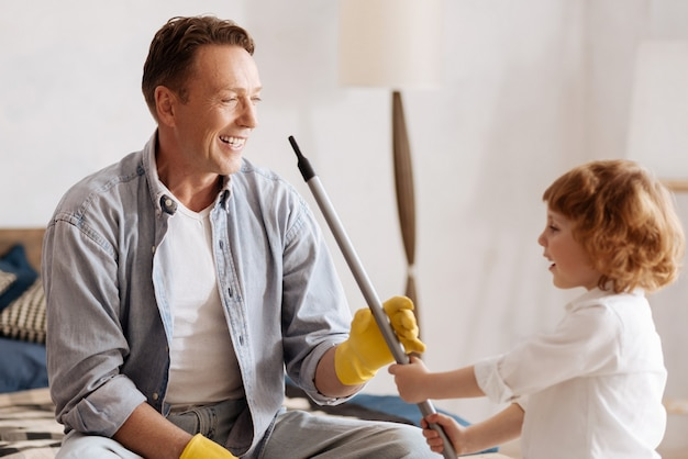 Expressing positivity. positive delighted father keeping smile on face while looking at his child and going to do cleaning