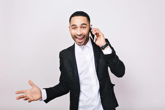 電話で話している若い成功した実業家の真の明るい肯定的な感情を表現します。スタイリッシュでモダンな労働者、マネージャー、成功、喜び、幸福。