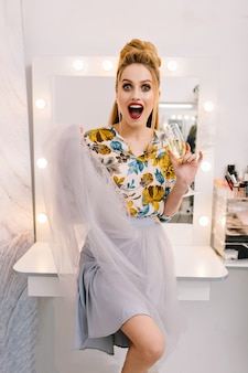 Expressing true positive emotions of fashionable pretty model in tulle skirt, with luxury coiffure, makeup, glass of champagne in hairdresser salon