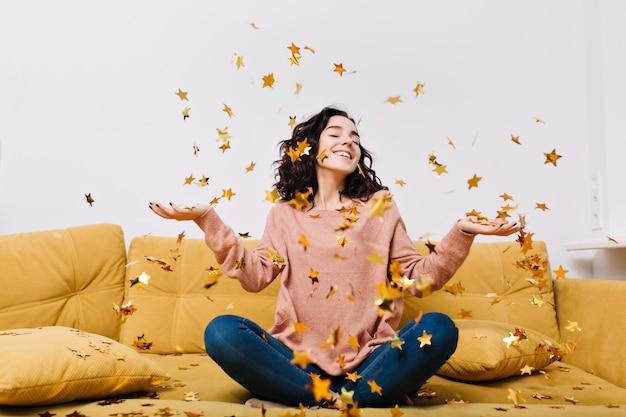 Выражение истинных положительных эмоций молодой радостной женщины со стриженными кудрявыми волосами, развлекающейся падающими мишурами на диване в современной квартире. домашний уют, радость, улыбка