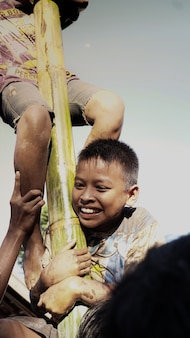 The expression of a child who is in pain but can still smile in a greasy pole game