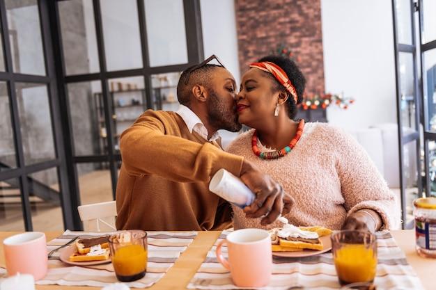愛の表現。彼女の近くに座っている間彼の妻にキスする楽しいアフロアメリカ人男性