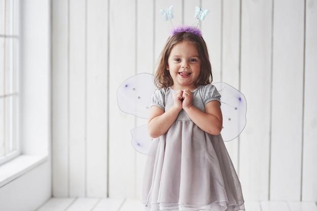 Выражение ожидания подарка. красивая маленькая девочка в костюме феи весело позирует для фотографий.