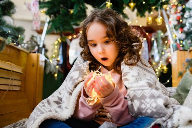 격자무늬로 덮인 곱슬머리 소녀의 얼굴 표정, 크리스마스와 새해 나무 배경에 앉아 빛나는 화환 조명을 손에 들고