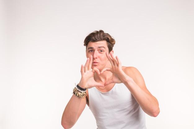 Выражение, чувства и концепция жестов - красивый парень делает сердце пальцами над белой стеной.