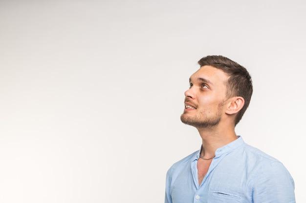 表現と人々の概念-コピースペースで白い壁を見上げるハンサムな陽気な若い男。