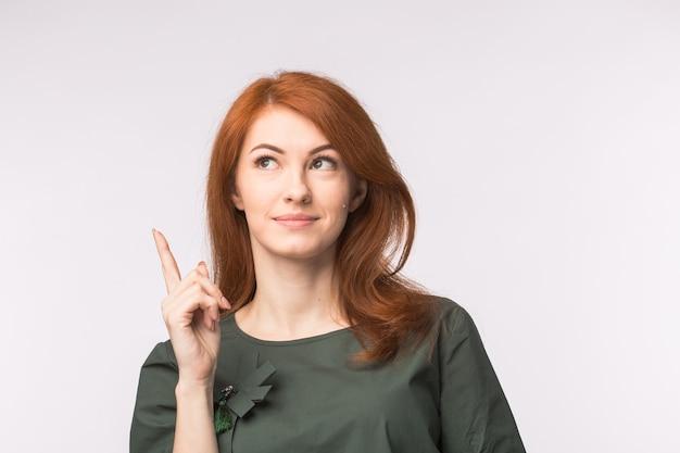 Выражения и люди концепции. молодая женщина с рыжими волосами, показывая жест идеи над белой