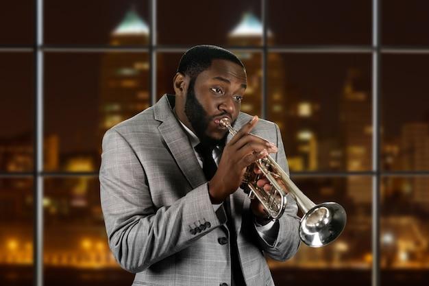 Выразительный афро-парень, играющий на трубе.