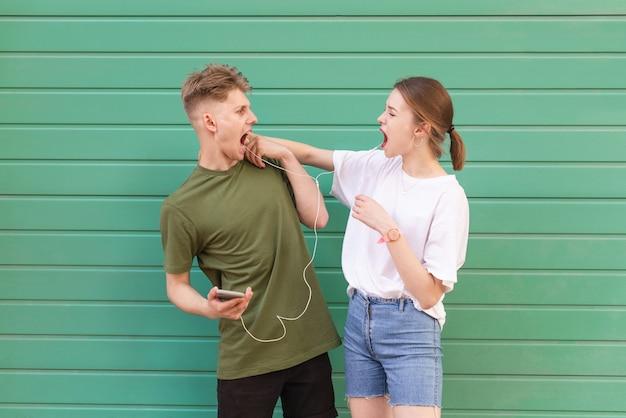 녹색 헤드폰에서 음악을 듣고 표현 재미있는 커플