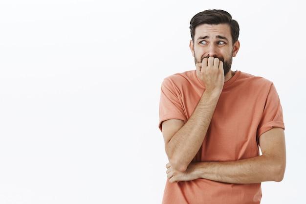 オレンジ色のtシャツで表現力豊かなひげを生やした男